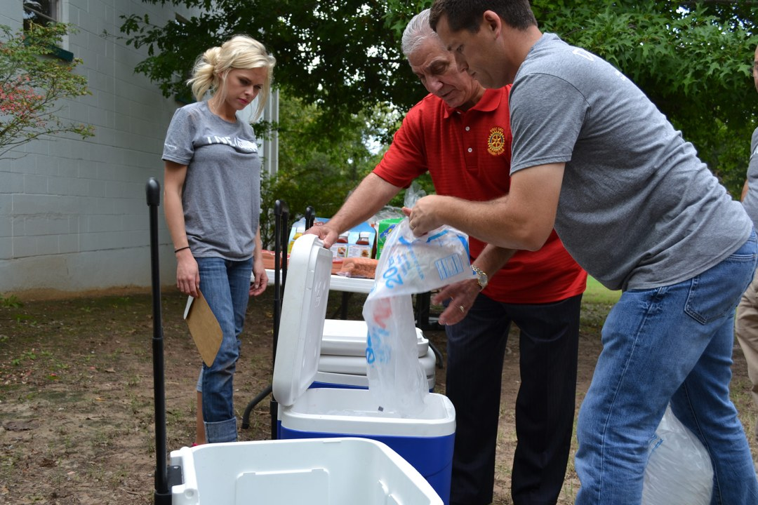Volunteers with Tapstone Energy and West Rotary stock a cooler with ice.