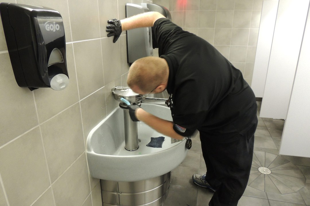 A team member cleans the sink area at a Work Projects location.