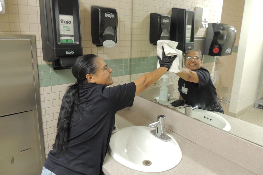 A custodial crew member cleans the mirror inside a restroom.