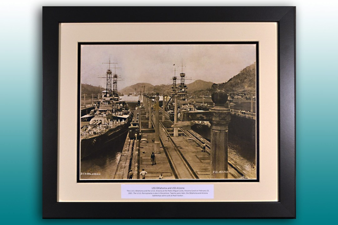 A framed image of the USS Oklahoma and USS Arizona.