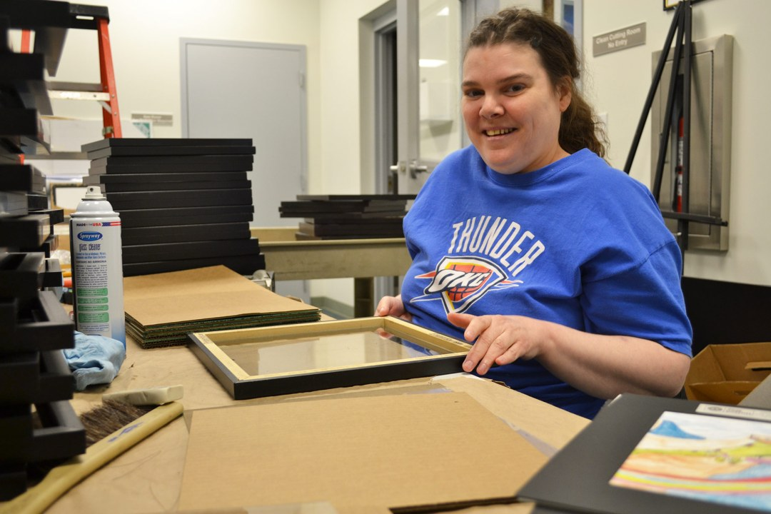 Julie smiles as she assembles diploma frames.