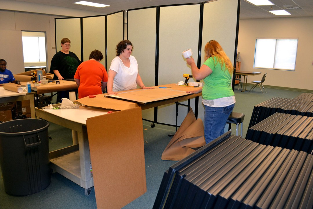 Several individuals at DRTC assembling picture frames.
