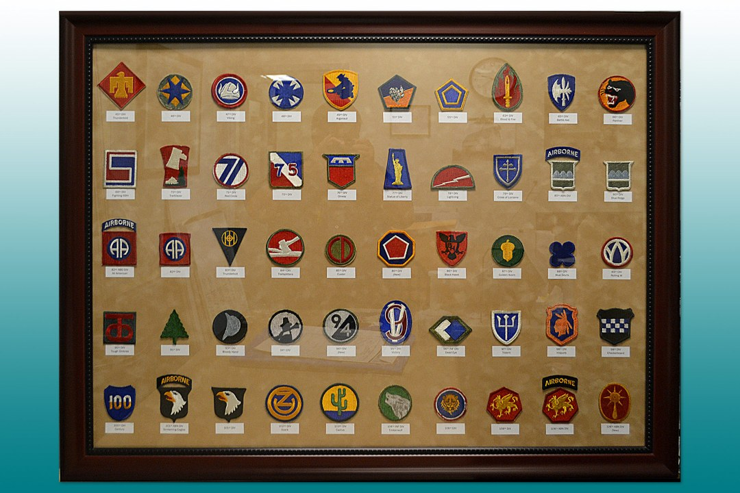 Several patches framed by Wyman Frame for the OK Military Department.