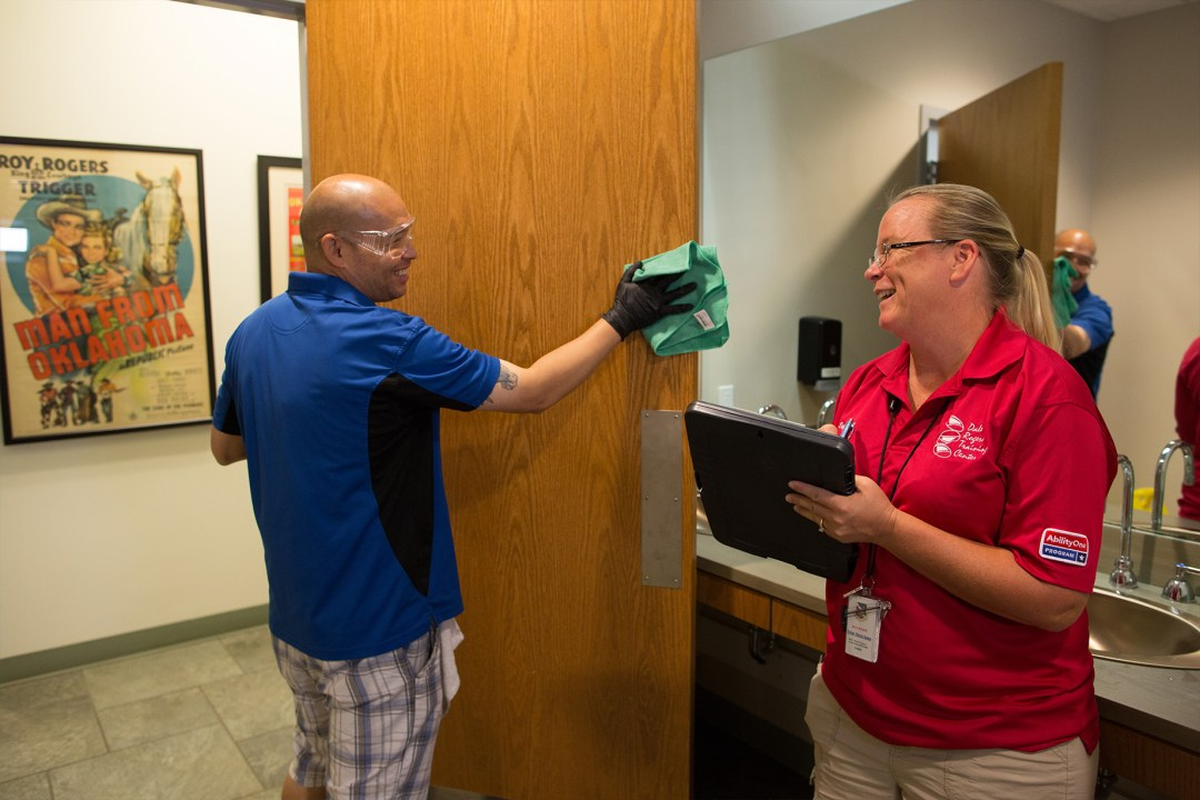 A supervisor smiling, holding a clipboard, and looking at George who is cleaning a door.