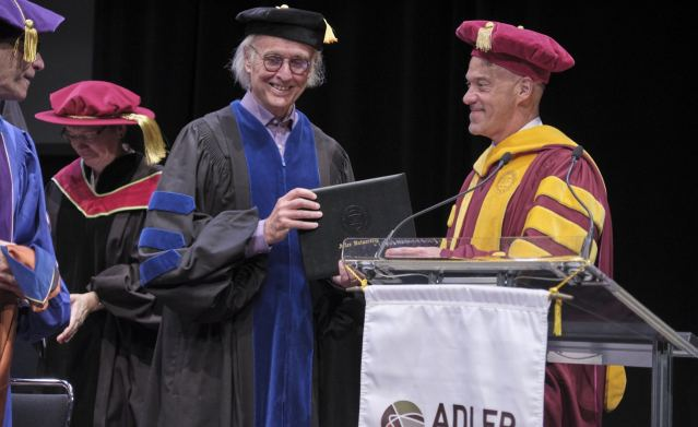 Man receiving a degree on stage at a university commencement ceremony