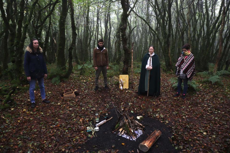 Saison sombre : nous voyons 4 personnes dont un sacerdote dans les bois en cercle autour d'un foyer dont le feu n'est pas encore allumé.