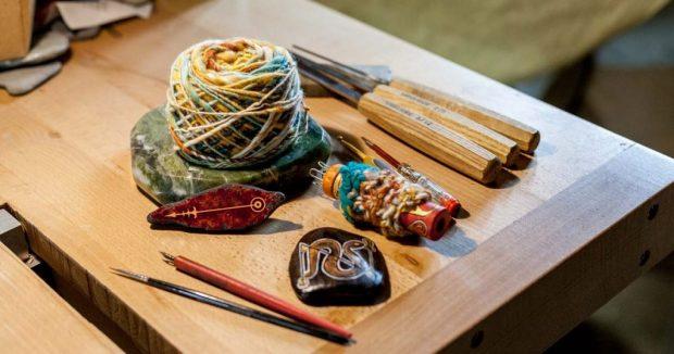 On voit différents outils des Artisans qui se sont retrouvés pour fêter Lughia : pelote de laine filée main, tricotin, pierre peinte, ciseaux à bois, tournevis électrique, plumes à dessin...