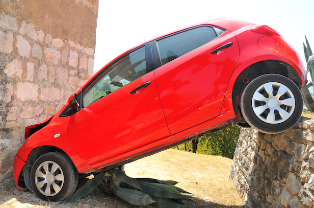 A small red car driven over a wall and crashed into the wall of a church, then wedged at an angle