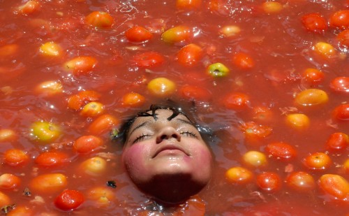 A child rests inside tomato pulp as part of the celebration of Holi in Hyderabad India on February 28 2010 500x309 A child rests inside tomato pulp as part of the celebration of Holi in Hyderabad India on February 28 2010