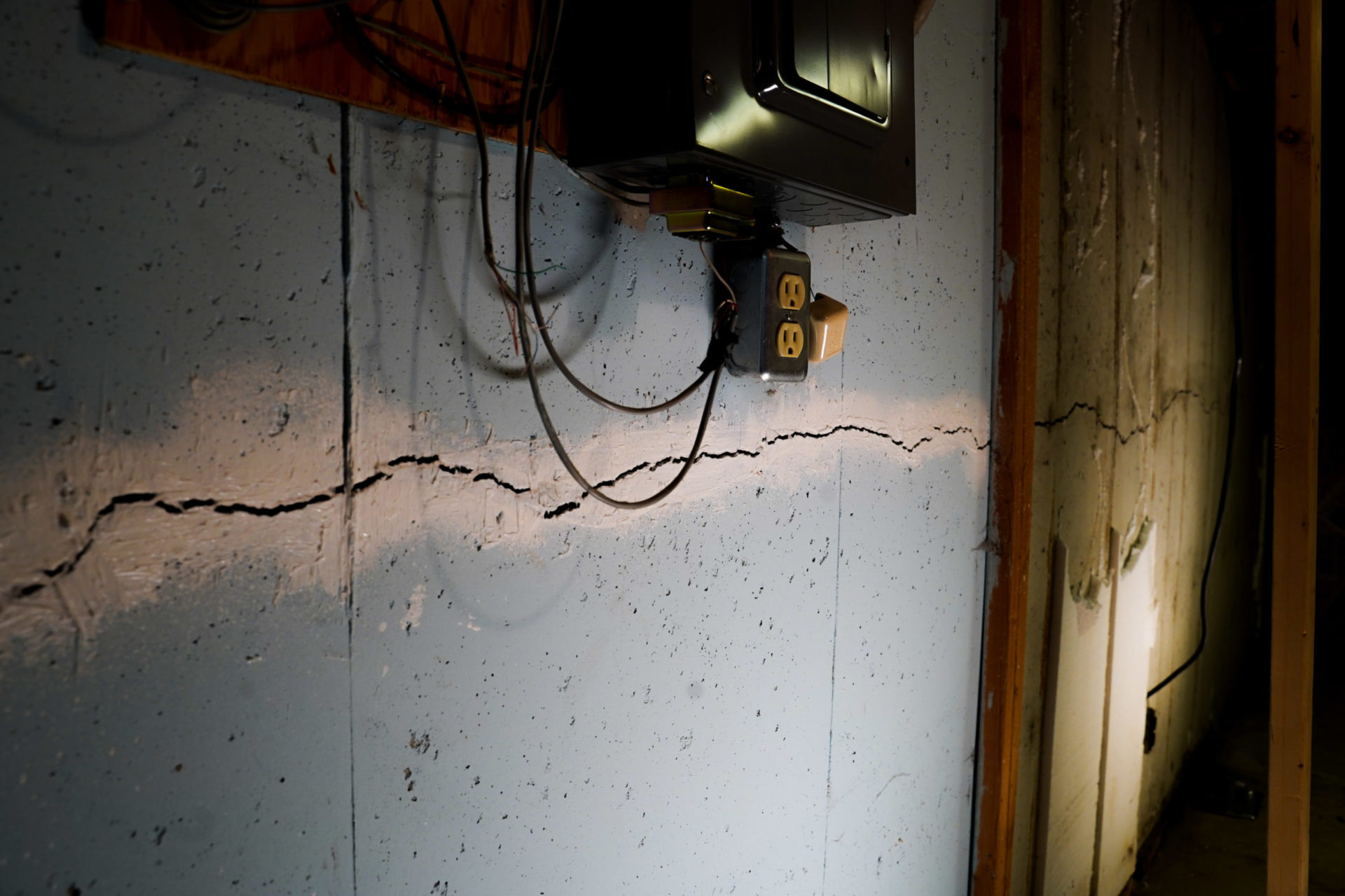 Horizontal wall crack on blue wall underneath TV in basement