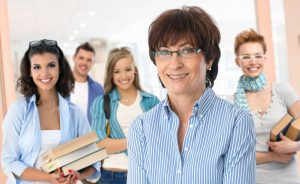 37664104 - portrait of happy senior female teacher with group of students in background.