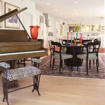 Gallagher's walnut grand piano is a family heirloom. The antique piano bench, now covered in an animal-print fabric, is also a gift from her maternal grandparents. A complementary black-and-white print makes the dining chairs pop while surrounding two black-lacquer pedestal tables that serve as a unique dining arrangement. Gallagher purchased the colorful mix-and-match resin candlesticks in Paris.