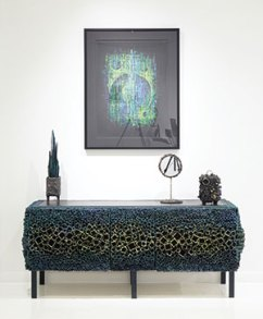 """Bearden's acrylic painting """"Five Moons"""" hangs above Serpentine Cabinet, whose barnacle-like sides and doors showcase his technique of welding pieces of square pipe to one another within a removable frame."""