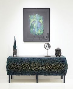 "Bearden's acrylic painting ""Five Moons"" hangs above Serpentine Cabinet, whose barnacle-like sides and doors showcase his technique of welding pieces of square pipe to one another within a removable frame."