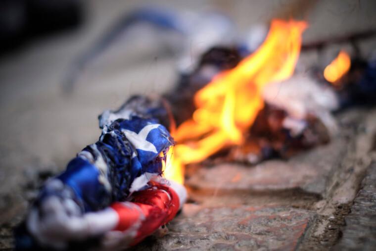 Протестуючі проти вбивства батька іранської бомби Мохсена Фахрізаде спалили американський прапор