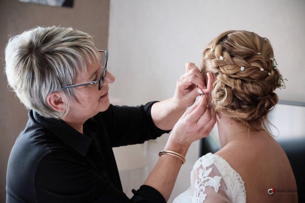 la maman aide sa fille à mettre ses boucles d'oreille de mariage