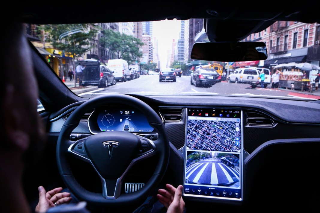 """A driver rides hands-free in a Tesla Model S equipped with Autopilot hardware and software in New York on Sept. 19. California says a true autonomous vehicle is one that is """"equipped with technology that has the capability of operating or driving the vehicle without the active physical control or monitoring of a natural person."""" (Christopher Goodney/Bloomberg News)"""