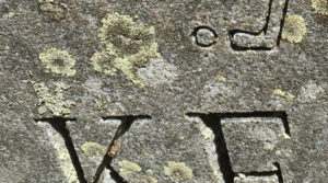 lichen obscuring lettering on tombstone