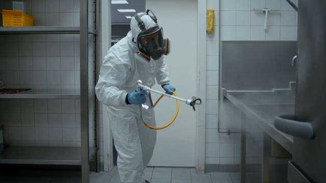 User disinfecting with spray in an industrial kitchen