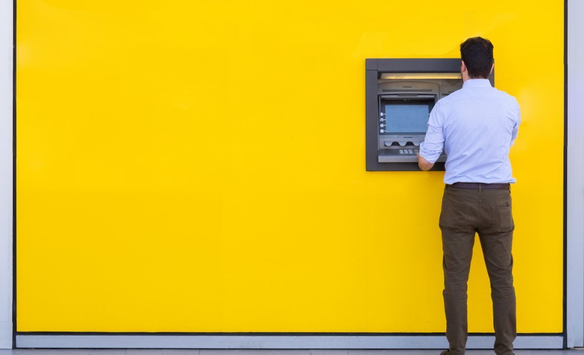Man standing by yellow wall using ATM