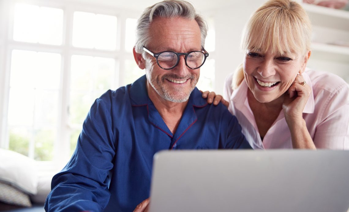 Mature Couple At Home Looking Up Information Online Using Laptop