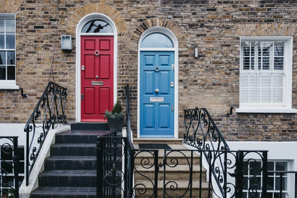 Bright blue and red doors on a traditional English house in London, UK.