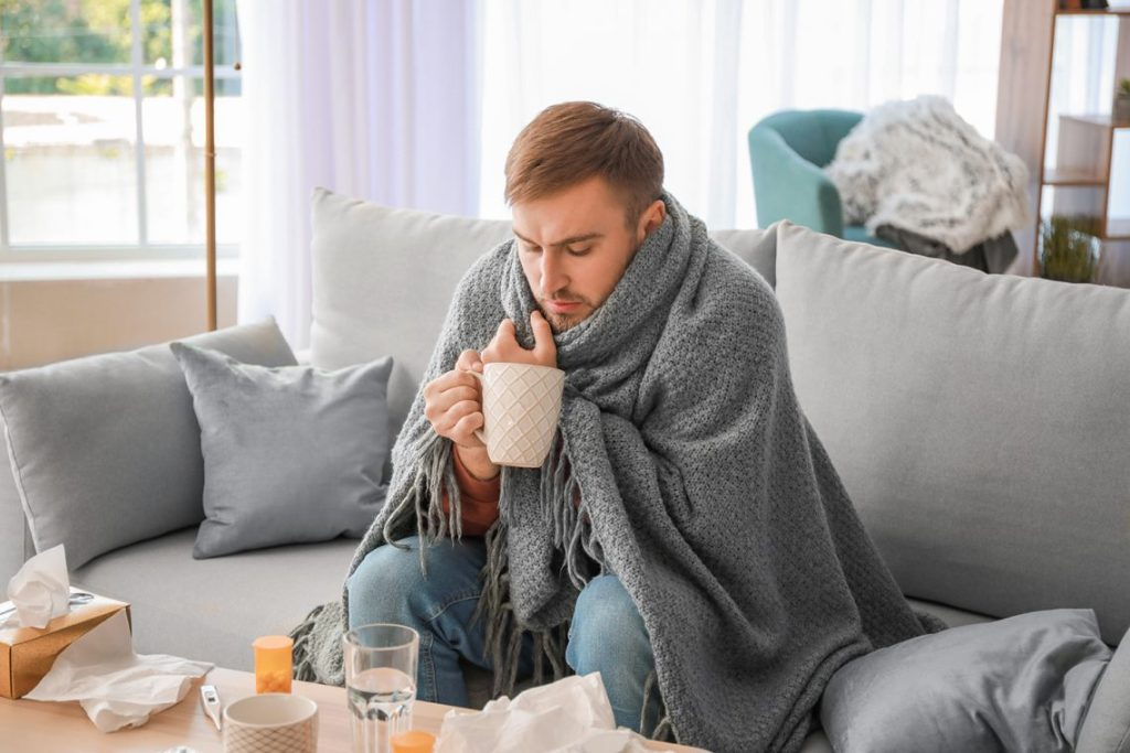 Man unwell, felling ill. Wrapped in blanket with hot drink