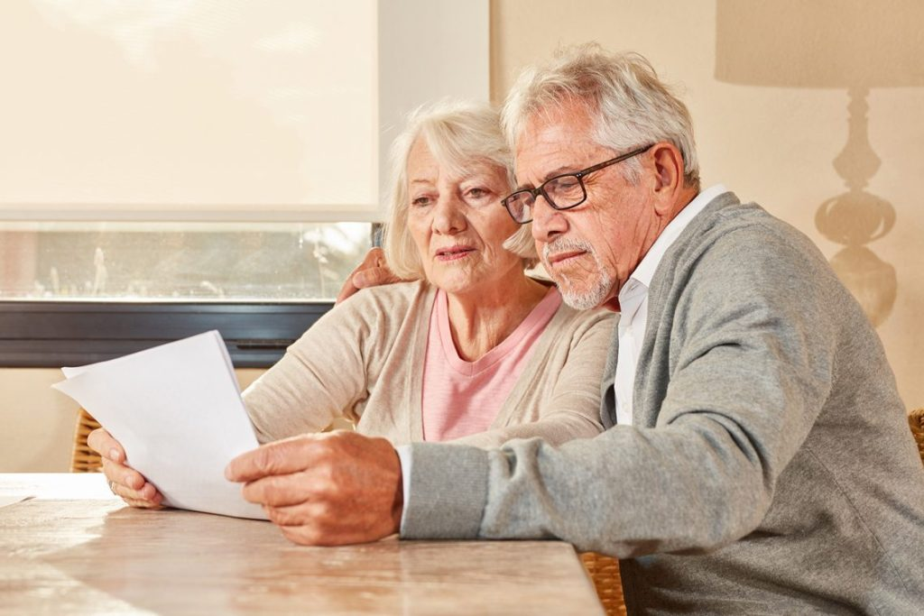 Elderly woman and man looking at letter. Pensioners