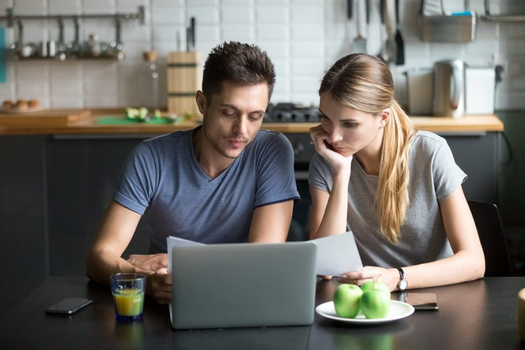 Young couple sat by laptop applying for a loan