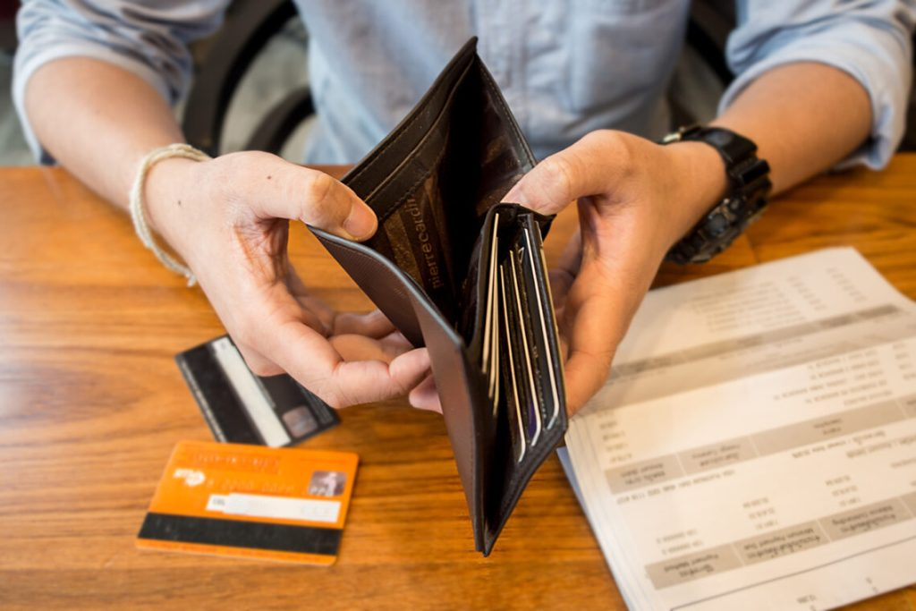 Man holding wallet open which is empty. Credit cards and bills on table.