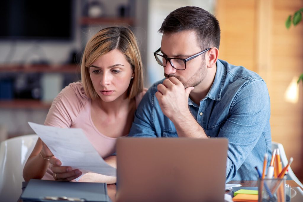 Worried couple sat by laptop with paperwork in hand.