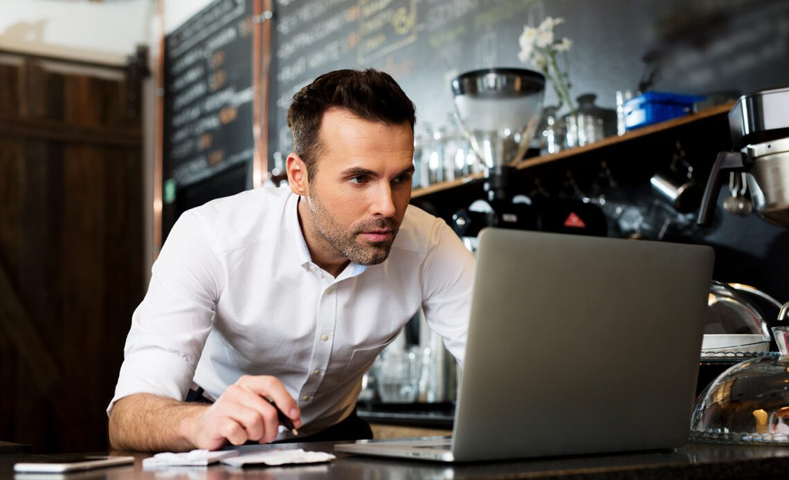 Small business owner (coffee shop) using laptop.