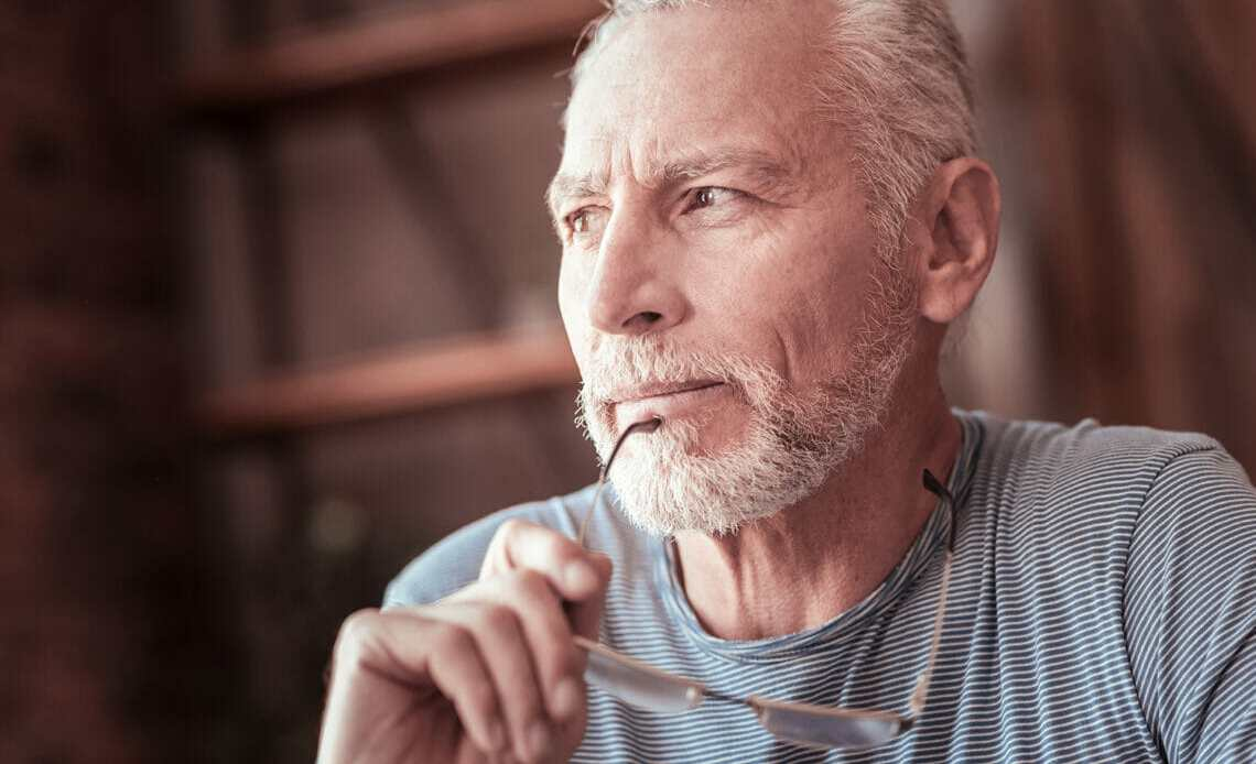 Elderly man thinking and holding glasses