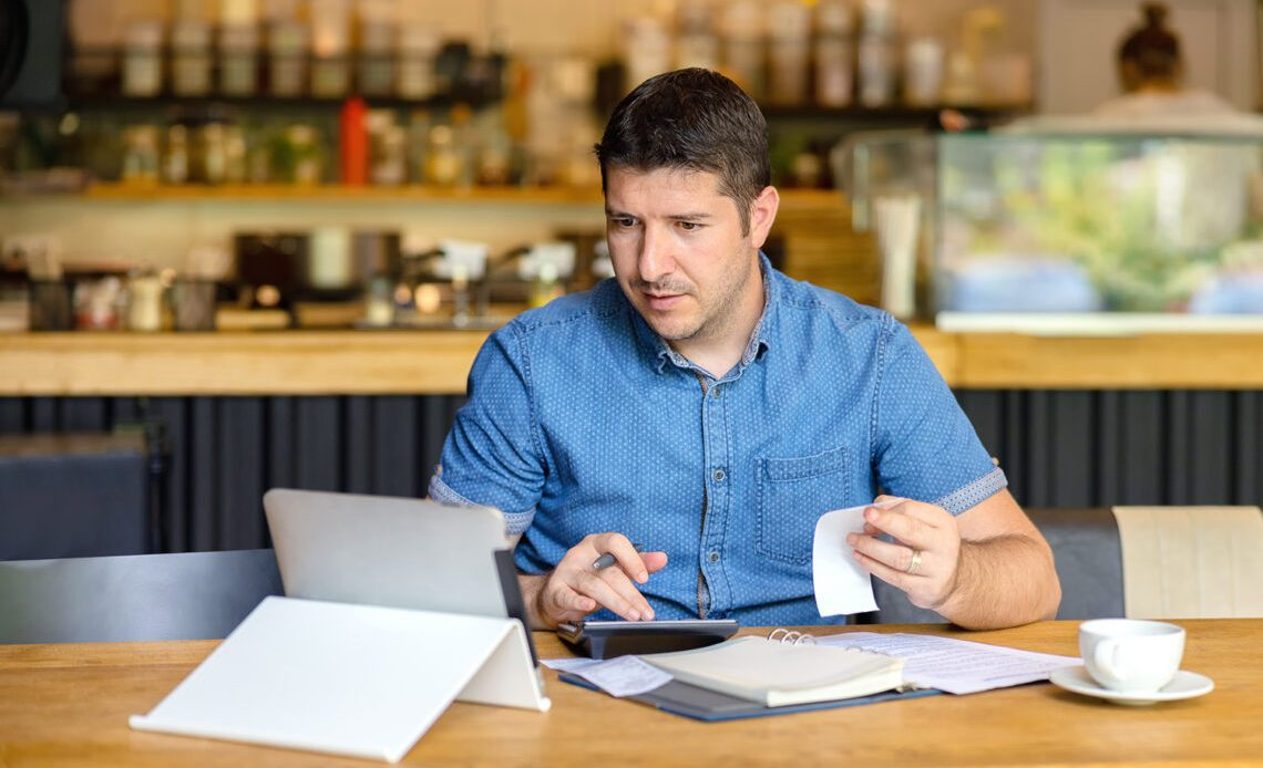 Restaurant business owner looking over budget on laptop