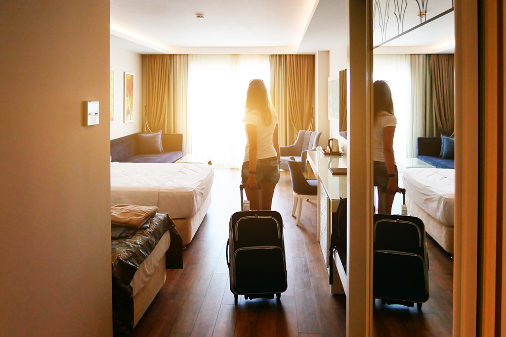 Women with suitcase in hotel room