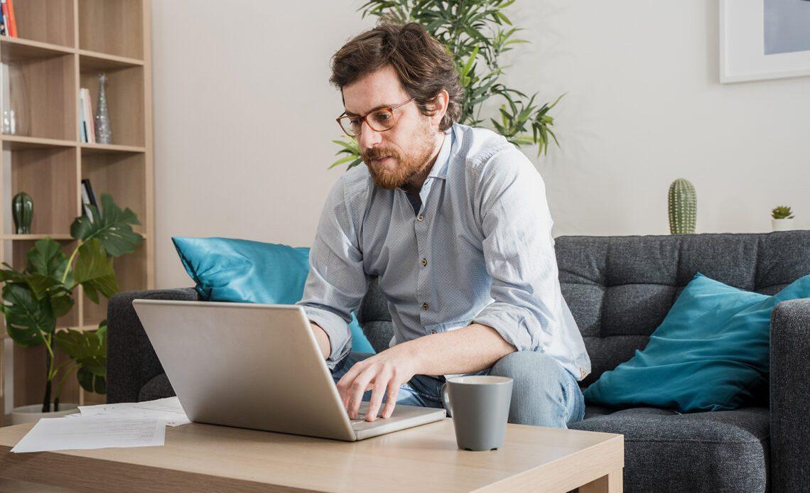 Man sat on sofa using laptop on coffee table