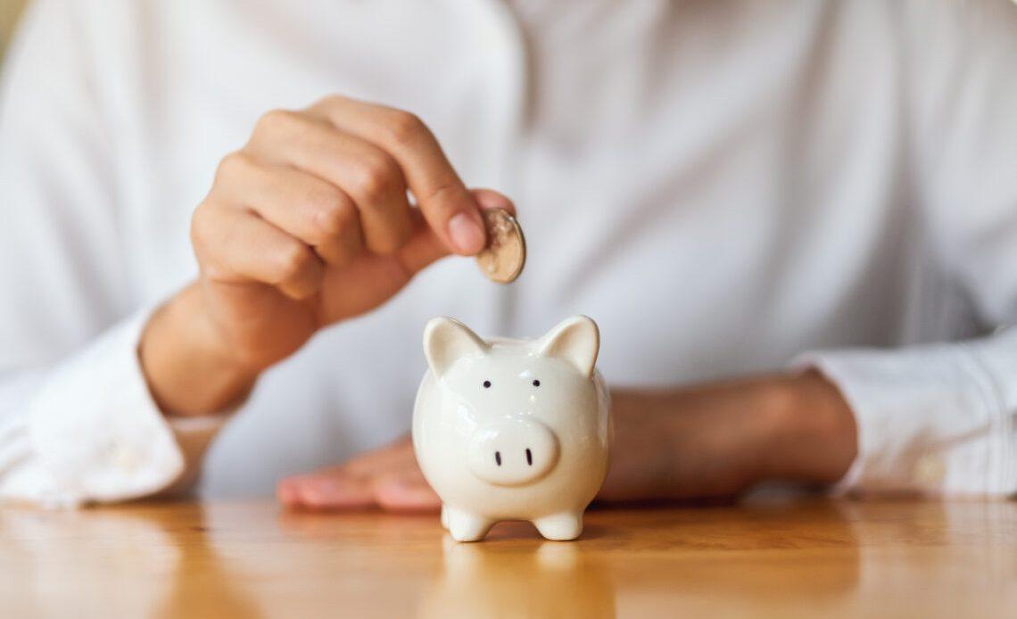 Women putting money into piggy bank for saving money.