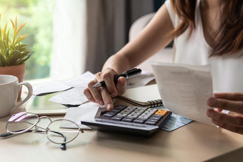 Women using calculator to budget.