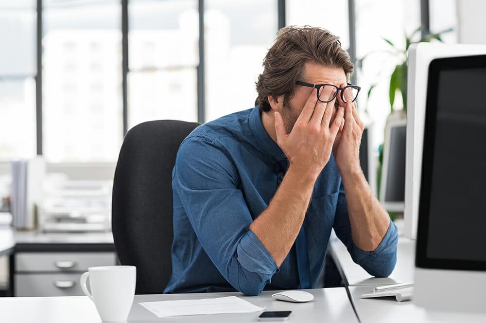 Stressed business man sat at desk.