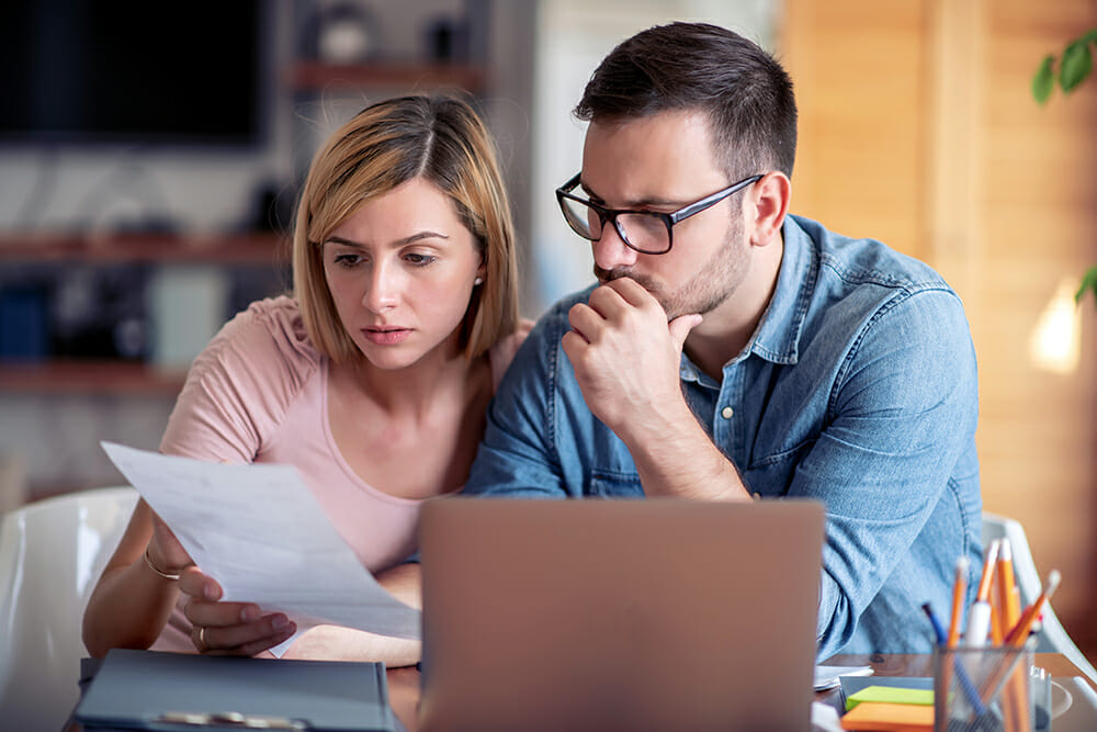 Worried couple sat by laptop, holding paperwork