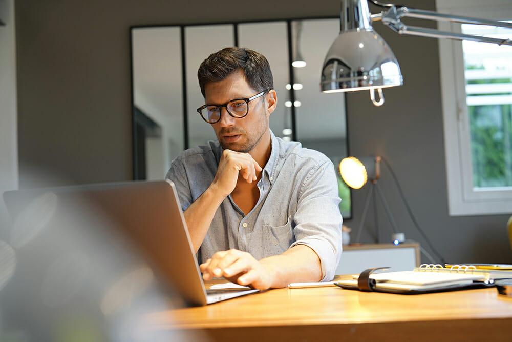 Man thinking. Using laptop at desk.