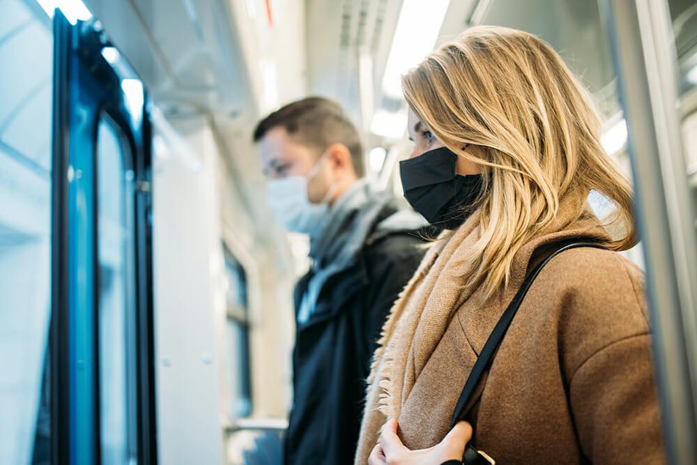 Man and women wearing mask on train