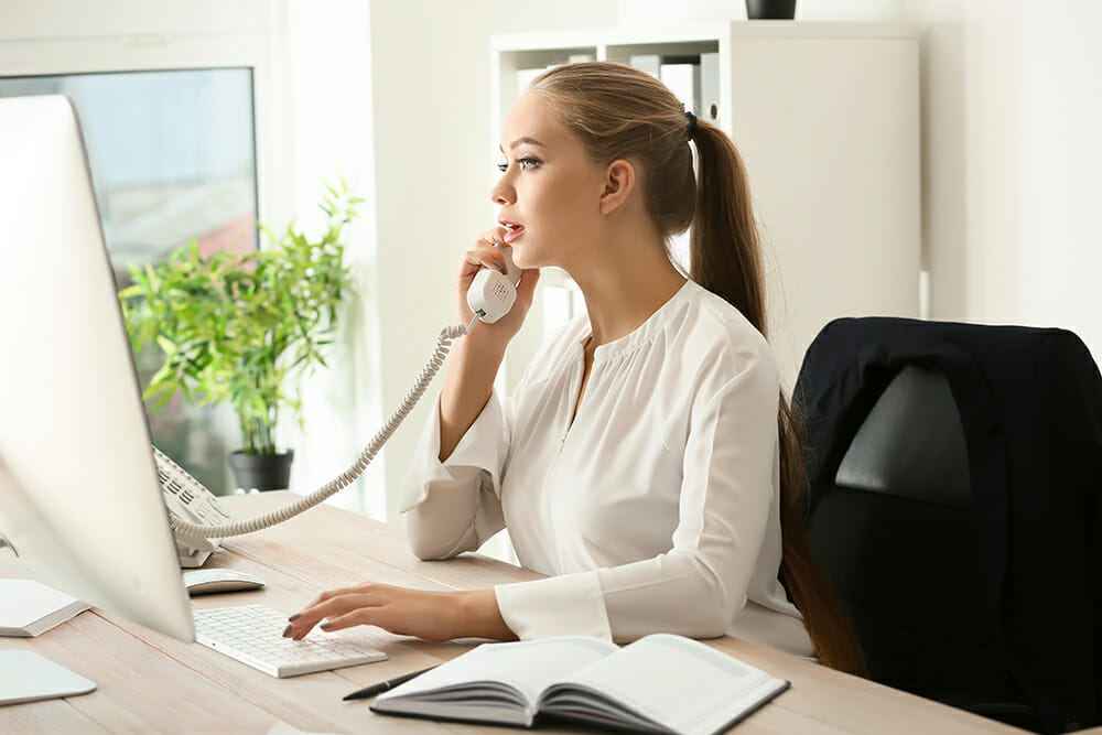Female Personal Assistant at desk. Using telephone and computer