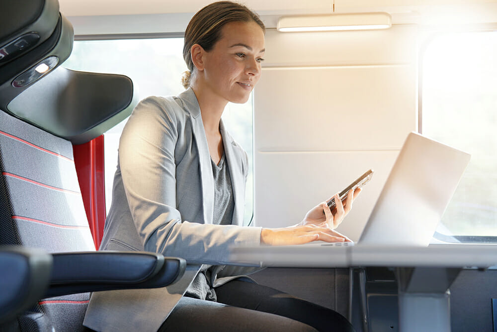Businesswoman on her cellphone and laptop computer on a train