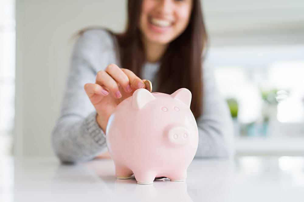 Smiling women placing money in pink piggy bank