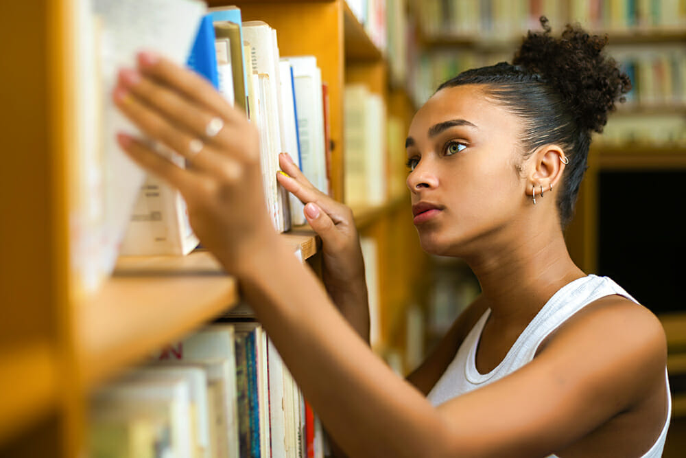 Student looking for book in library