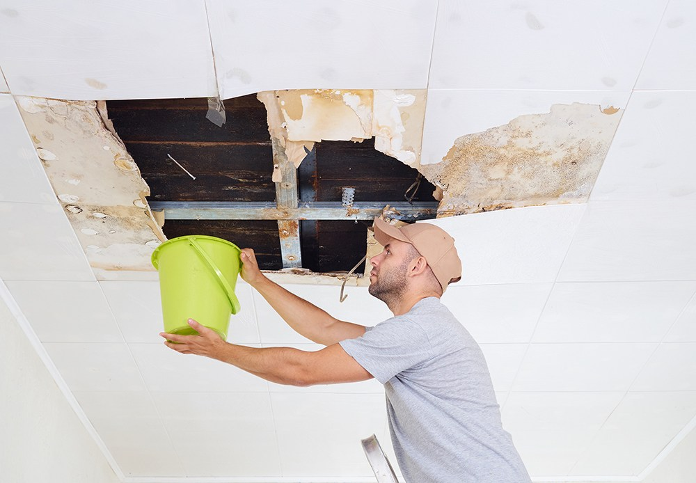Man collecting water in bucket from hole in the roof