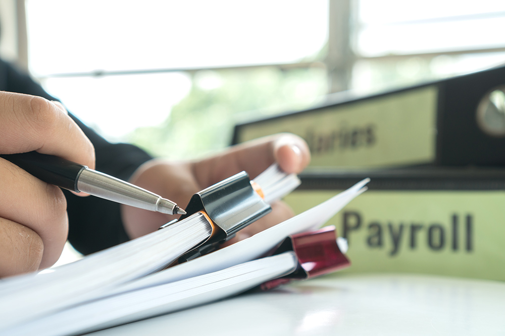 Payroll folder. Person holding files