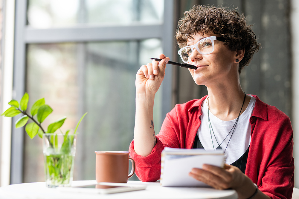 Women with glasses and pen sat at table with cup, plant and note book thinking