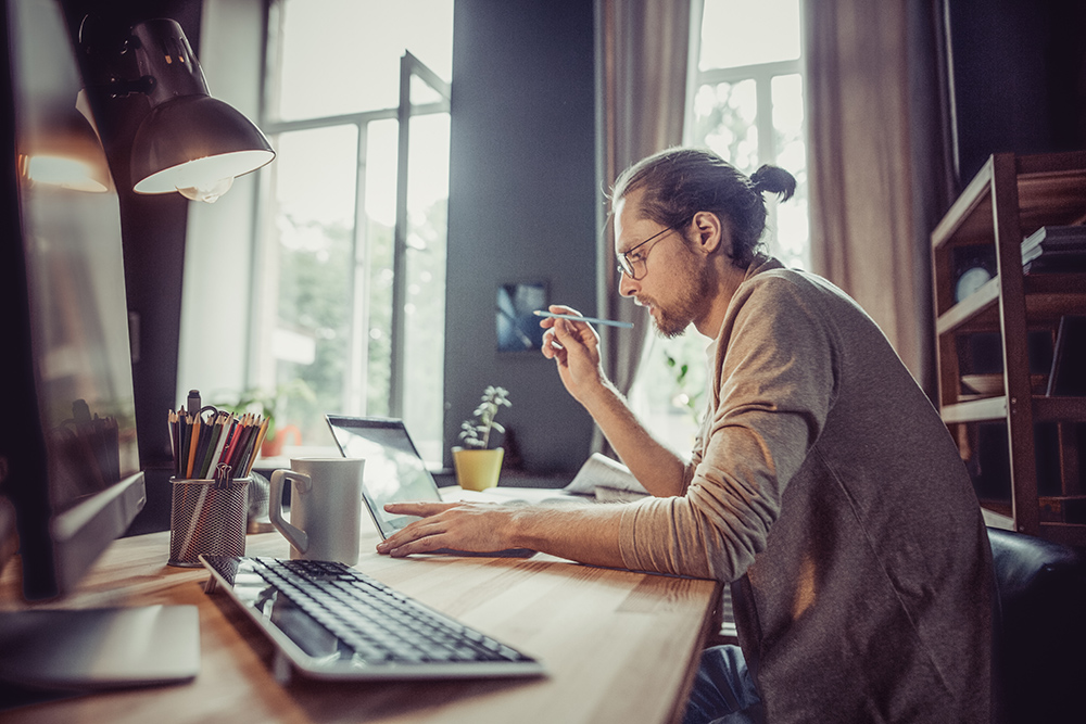 Young man with ponytail. Freelancer sat at desk with computer